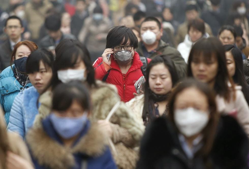 Ciudadanos de Pekín caminan por la calle con mascarillas